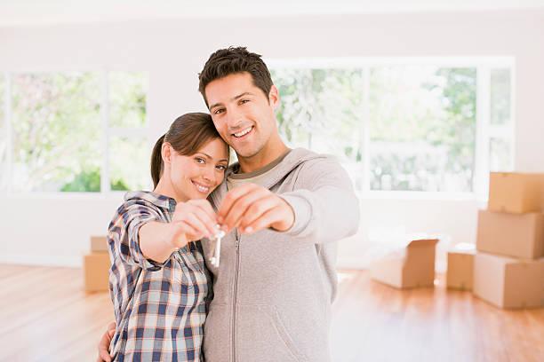 Couple qui tient les clés de la maison qu'il vient d'acheter