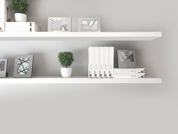 Deux étagères murales à fixation invisible avec de la décoration et une pile de livres