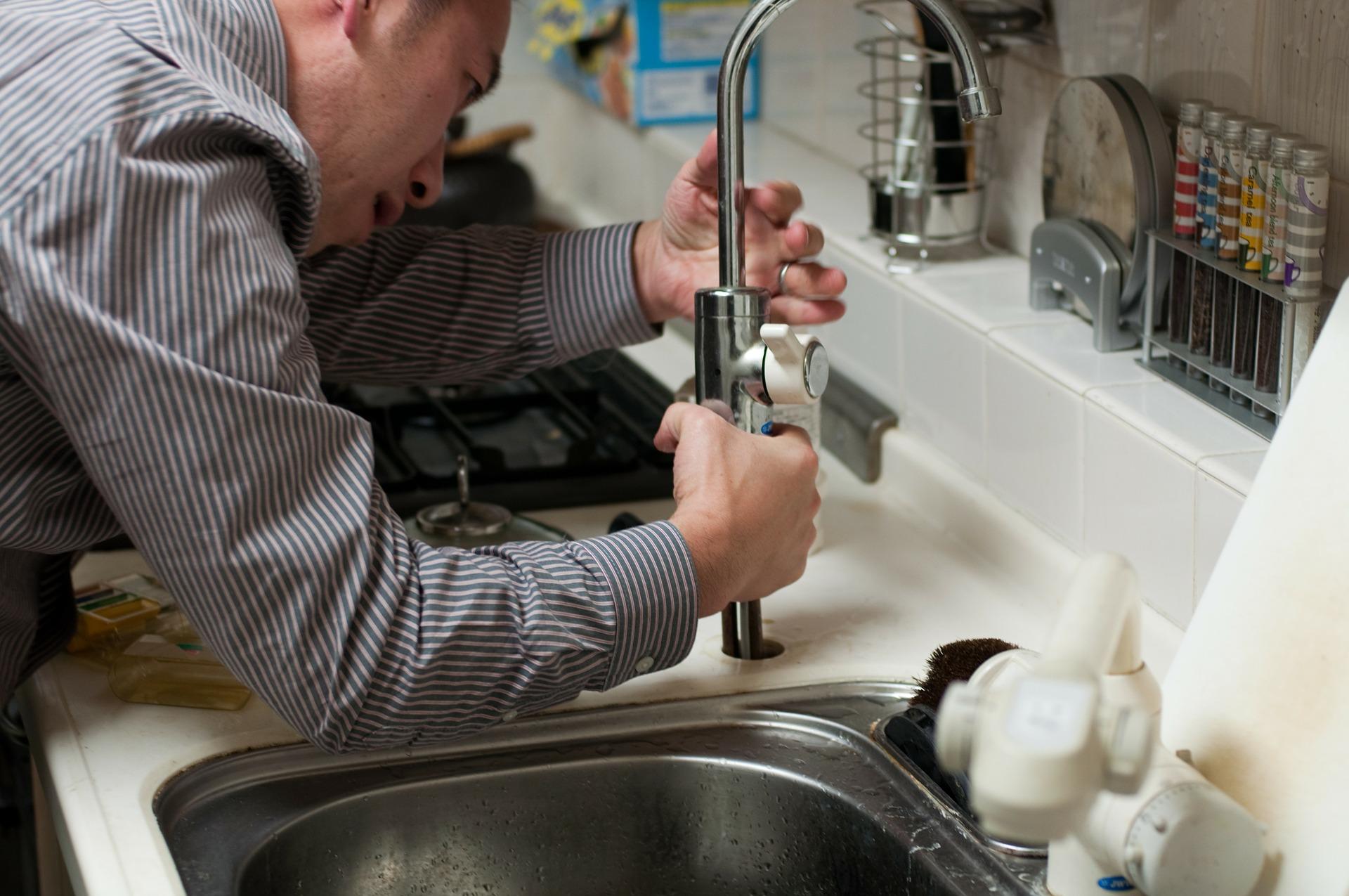 Un plombier en train de réparer un robinet d'évier