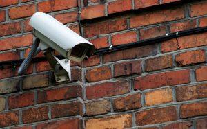 caméra de surveillance sur un mur en briques rouges