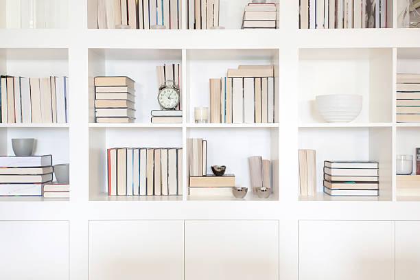 Gros plan sur une bibliothèque classique blanche avec plusieurs livres dans les cases