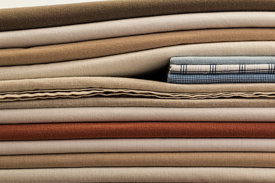Linge de lit plié et rangé dans une pile de draps