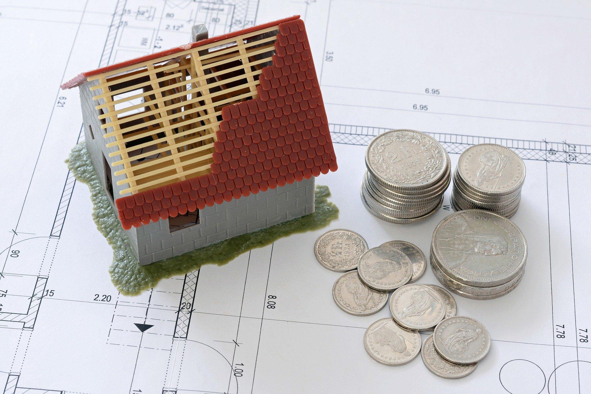 Petite maison en construction et pièces de monnaie posées sur un plan de construction